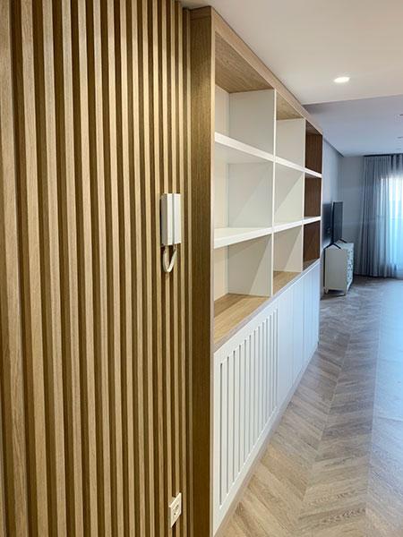 Panelado de listones de haya integrado con mueble librería en salón