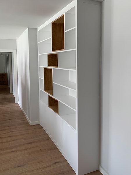 Vista lateral de mueble librería lacado blanco en pasillo