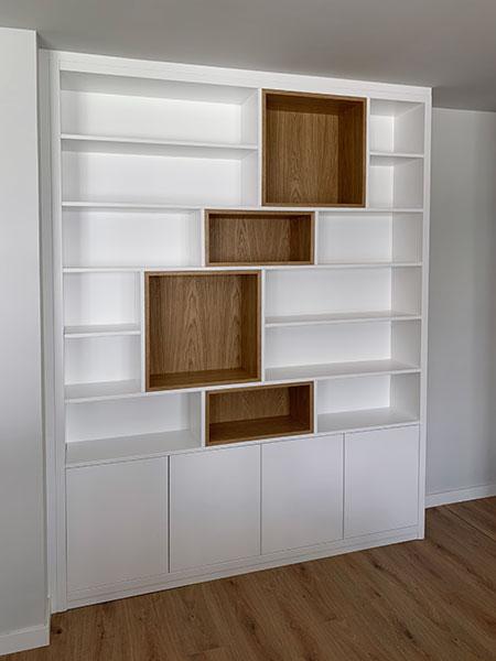 Mueble librería con baldas lacadas en blanco y módulos en madera de nogal