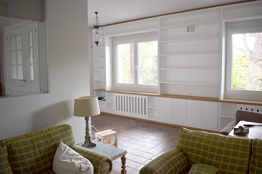 Librería lacada en blanco con puertas, cubre radiadores y repisa de madera