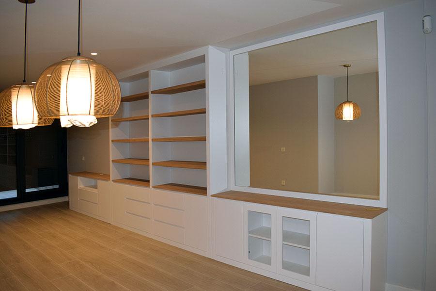 Librería mural lacada en blanco con puertas y cajones, estantes en madera de haya y espejo integrado