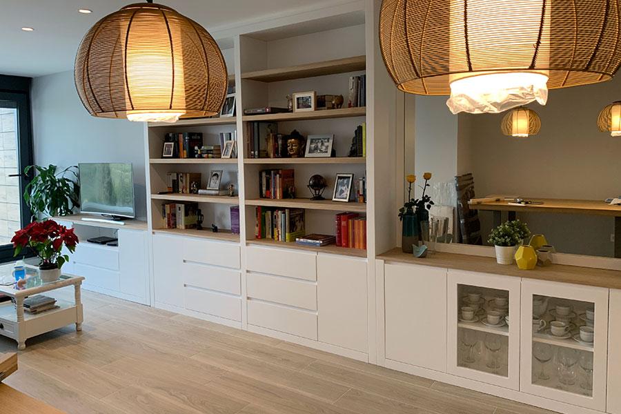 Librería mural para salón con puertas y cajones en blanco y baldas de madera natural